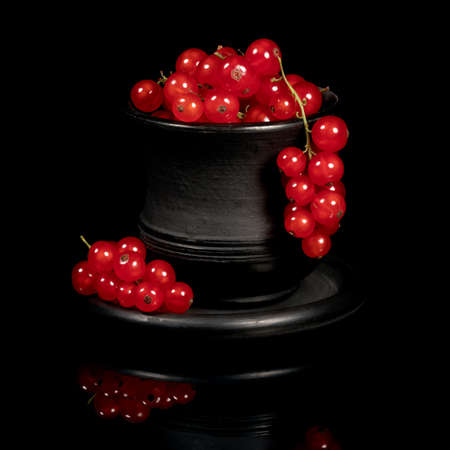 Several bunches of red currants in a black cup on a black background. Full depth of field 写真素材