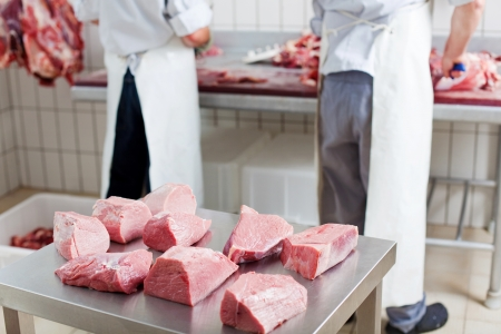 Several portions of fresh cut meat resting on a stainless steel workbench, with two butchers working on the background photo