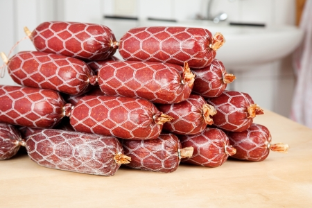 meat counter: A bunch of salami lying on a wooden plank Stock Photo