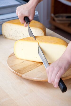 slicing: Worker slicing the cheese using double handed cheese knife Stock Photo