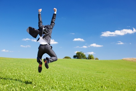 excited: Businessman jumping for joy celebrating a successful achievement in a lush green field under a blue sky Stock Photo