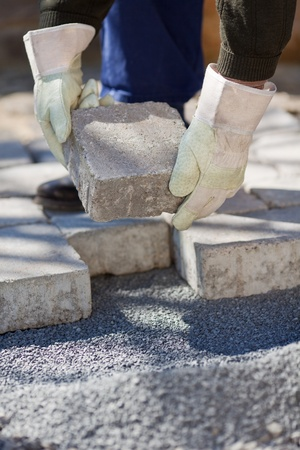 new way: Bricklayer paving a street in a close up shot