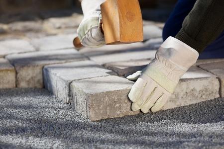 Cierre de mierda de trabajador de la construcción que fija un camino de ladrillos
