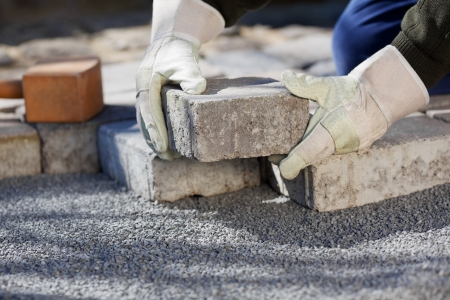 shit: Close up shit of construction worker paving the brick road