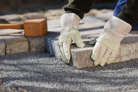 road worker: Construction worker fixing the pavestone on the road Stock Photo