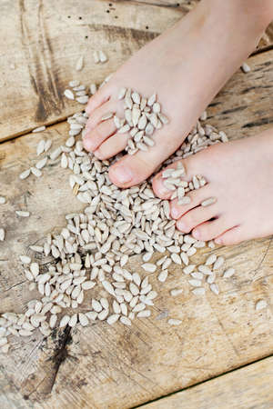 Child feet with s bunch of sunflower seeds on a wooden table photo