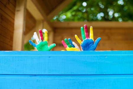 Children showing their colorful hands in the playhouse photo