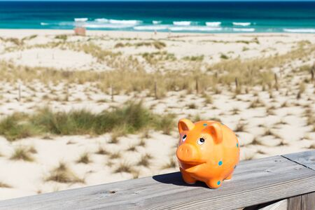 coinbank: piggybank standing on stage by the beach