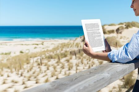 ereader: Mid adult woman reading e-reader at fence on beach Stock Photo