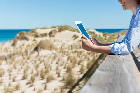 travel guide: woman by the beach leaning on wood and reading on tablet-pc