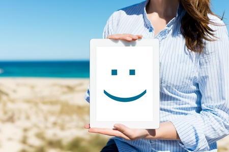 midsection: Midsection of mid adult woman displaying digital tablet with smiley face at beach