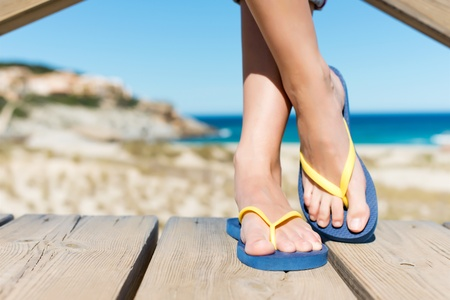 flip flop: Low section of woman wearing slippers while standing on board walk
