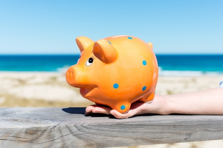 holiday budget: woman´s hand holding piggy bank by the beach Stock Photo