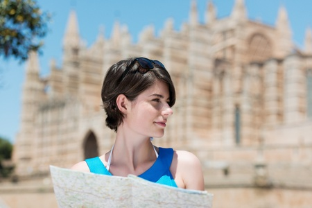 Lovely woman looking at something and holding streetmap outdoors photo