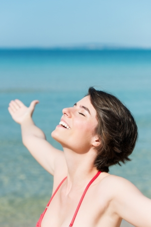 elation: Freedom beach woman smiling happy and serene with arms outstretched in free pose Stock Photo