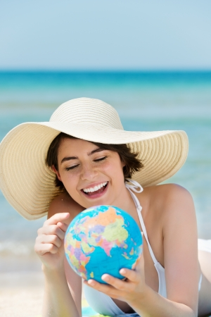 Attractive young woman in white hat pointing at globe in the beach photo