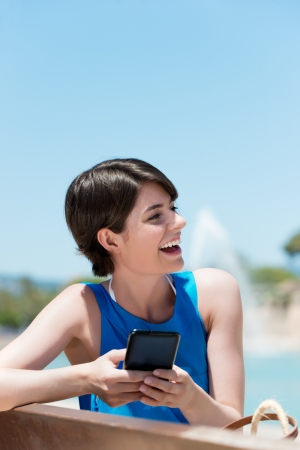 Happy cheerful woman texting through touch screen cell phone photo