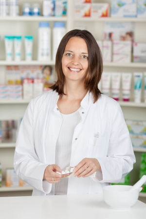 Midsection of female pharmacist with tablets at pharmacy counter photo