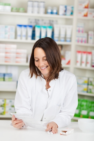 mid adult female: Mid adult female pharmacist reading prescription paper in pharmacy Stock Photo