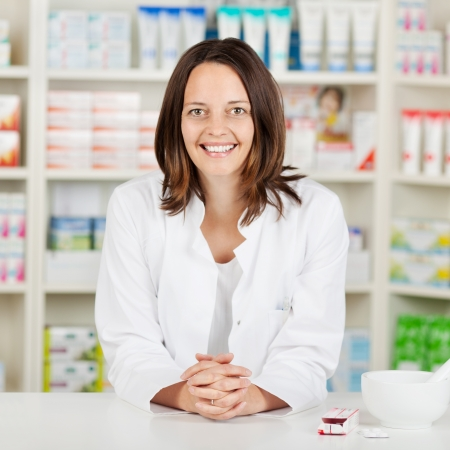 Portrait of mid adult female pharmacist with hands clasped leaning on pharmacy counter photo