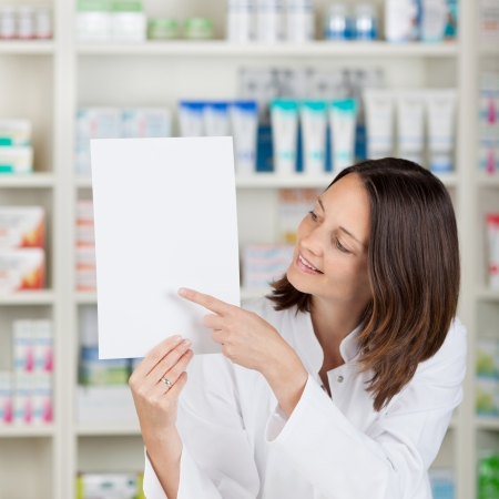 store sign: Portrait of mid adult female pharmacist pointing on blank paper at pharmacy