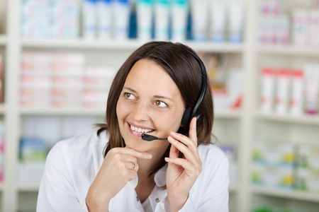 conversing: Mid adult businesswoman conversing on headset in pharmacy Stock Photo