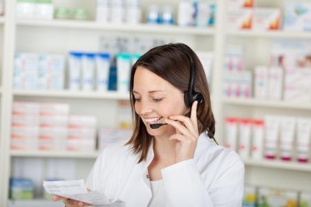 mid adult female: Happy mid adult female pharmacist conversing on headset in pharmacy