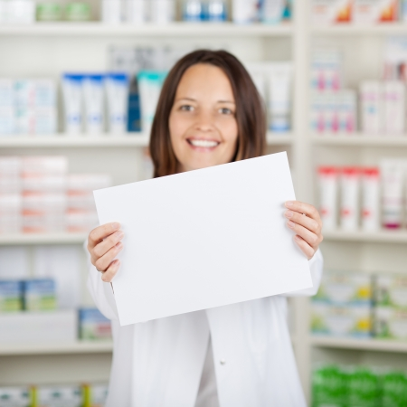 Portrait of mid adult female pharmacist holding blank paper at pharmacy photo