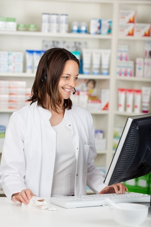Mid adult female pharmacist conversing on headset in pharmacy photo