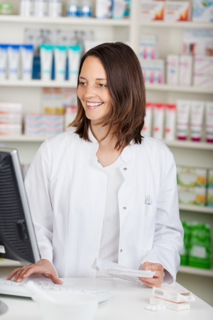 drug store: Mid adult female pharmacist using computer while holding prescription paper at desk