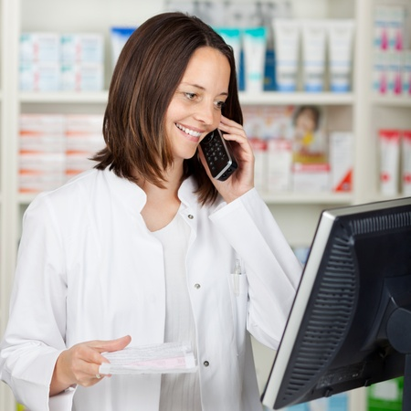 Mid adult female pharmacist using cordless phone while looking at computer in pharmacy photo