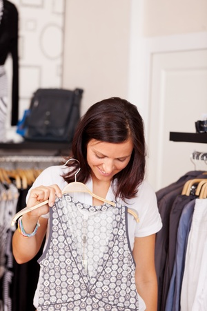 Mid adult woman looking at dress in clothing store photo