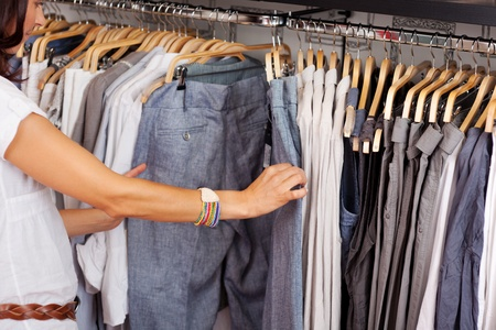 trouser: Mid adult woman choosing trouser from rack in clothing store