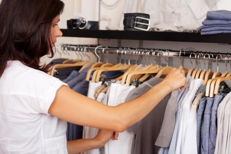 coathangers: Mid adult woman choosing shirt from rack in clothing store