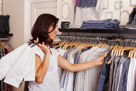 mid adult female: Mid adult female customer choosing clothes from rack in clothing store