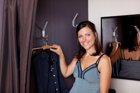 Portrait of happy woman with new shirt standing in changing room photo