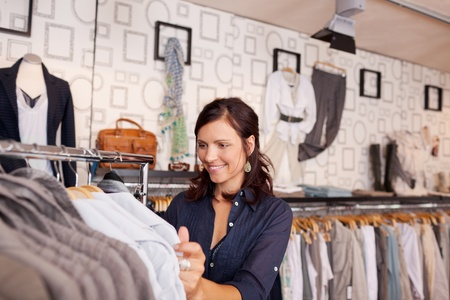 Portrait of smiling woman looking at shirt in clothing store photo