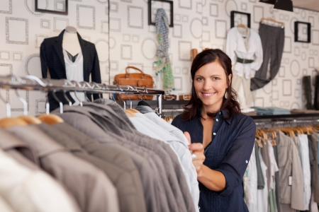 seasonal clothes: Portrait of happy female customer choosing shirt in clothing store Stock Photo