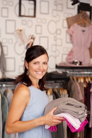 Portrait of happy smiling female customer holding stack of clothes in boutique photo