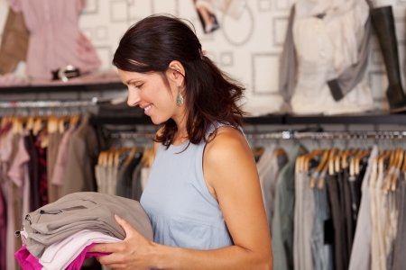 Portrait of happy Saleswoman holding stack of clothes in boutique Stock Photo - 20651429