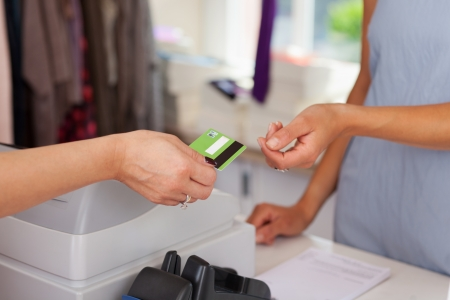 Closeup of saleswoman giving credit card to female customer at boutique counter photo