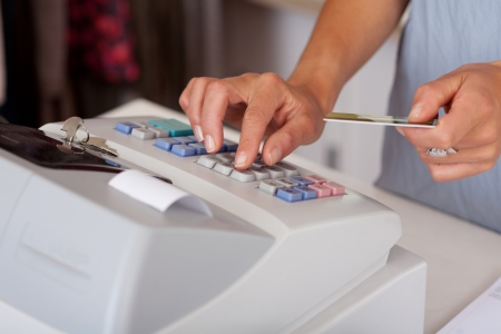 entering information: Midsection of saleswoman holding credit card while using cash desk at boutique counter