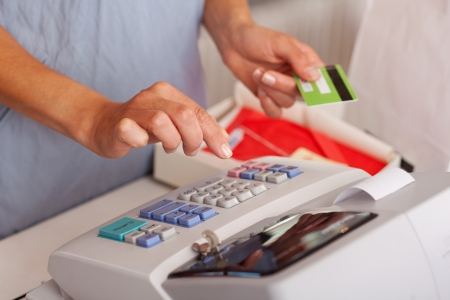 saleswoman: Midsection of saleswoman holding credit card while using ETR machine at boutique counter