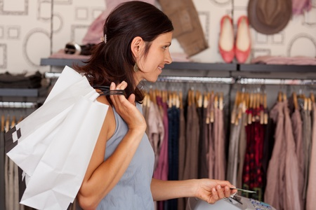 spendthrift: Mid adult female customer with shopping bags paying with credit card in boutique