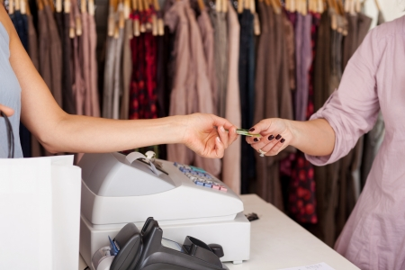 taking inventory: Female customer with shopping bag receiving credit card from saleswoman in boutique