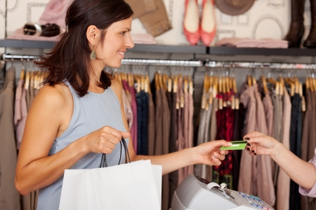 Mid adult female customer with shopping bags receiving credit card from saleswoman in boutique Stock Photo - 20651431