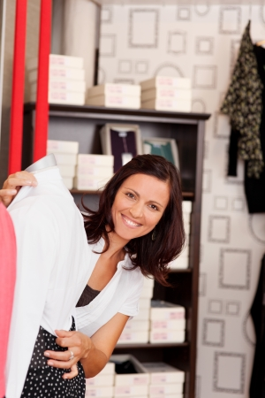 fitting in: Portrait of happy female customer checking shirts fitting in clothing store Stock Photo