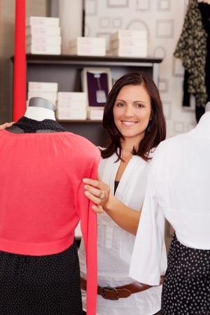 Portrait of happy woman examining clothes on mannequin in clothing store photo