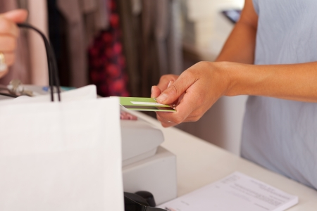 taking inventory: Midsection of saleswoman holding credit card from customer while using cash desk at boutique counter Stock Photo