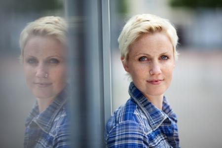Portret van een jonge blonde vrouw met sproeten leunend tegen een raam naar buiten, zodat haar hoofd is terug samen met haar